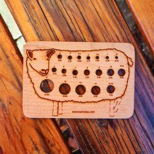 Stickmått med en bild på ett får, mäter stickor från 2 mm till 12 mm