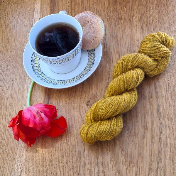 Färgen Assam tillsammans med en te kopp och en tulpan