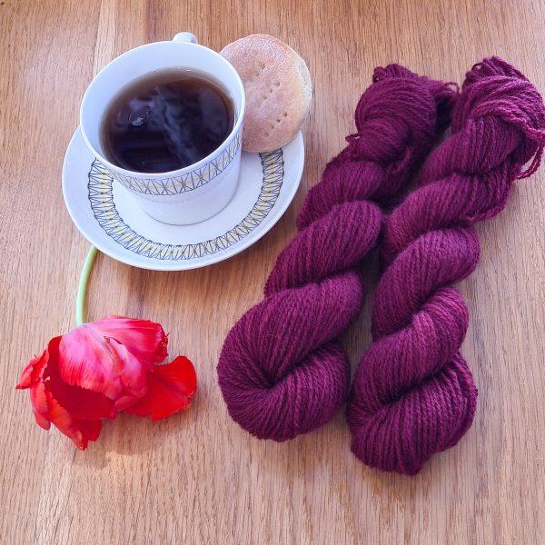 Färgen Hibiskus Te tillsammans med en tekopp och en tulpan